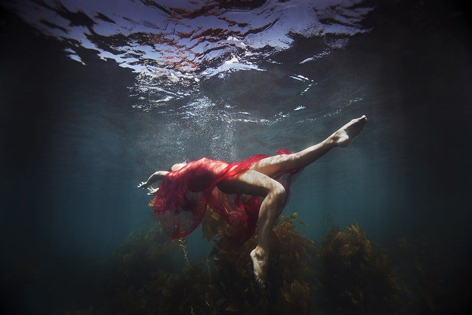 KELSEY WILHM LAYS IN THE OCEAN WITH RED FABRIC. (PHOTOGRAPH BY © JENNY BAUMERT 2013.)