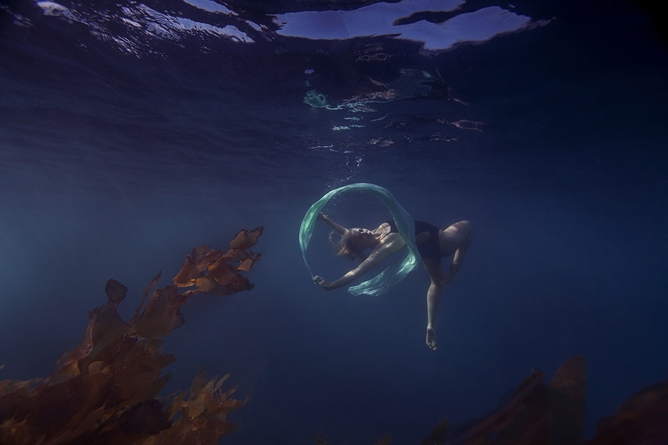 JANE AUSTIN IS SEEN TWIRLING FABRIC INTO CIRCLES IN THE OCEAN. (PHOTOGRAPH BY © JENNY BAUMERT 2013.)