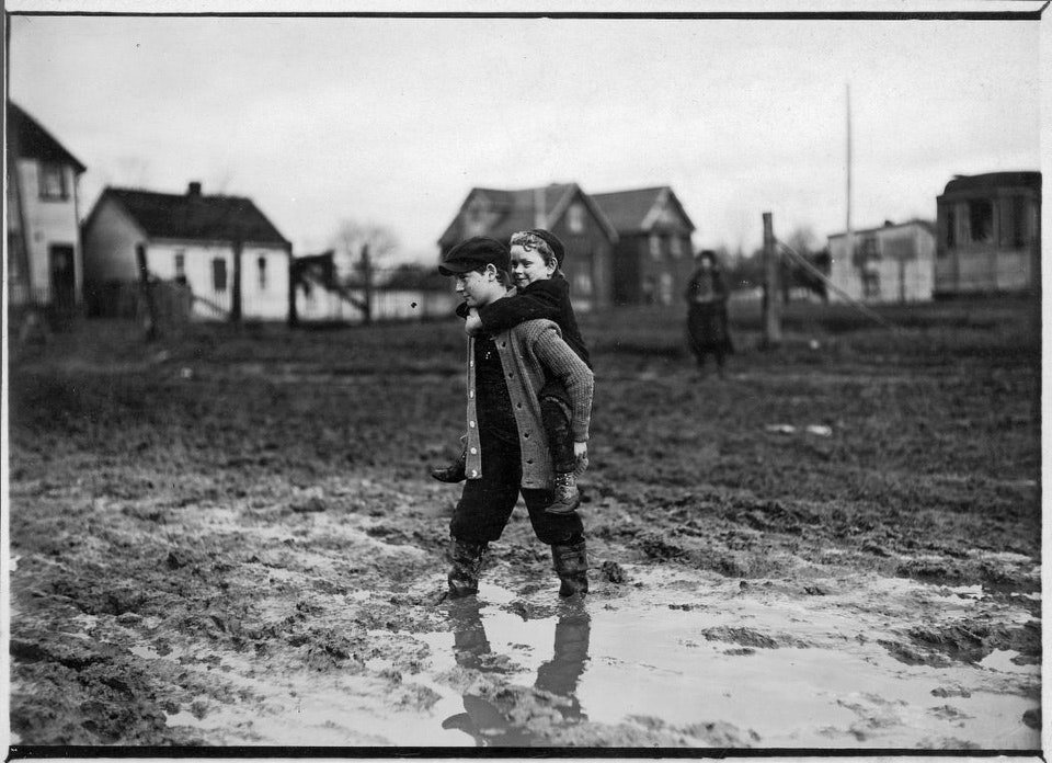 One child piggy-backs another across a muddy road, Earlscourt. - [between 1908 and 1920]