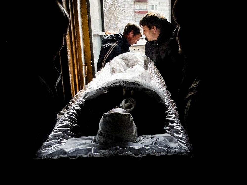 Женщину выносят из подъезда в гробу.