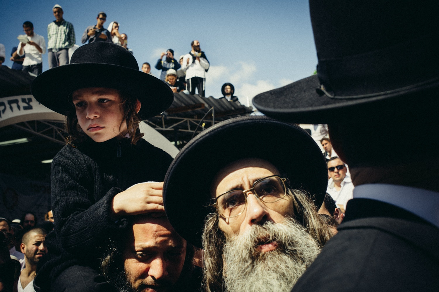 Young Hasid sits on the shoulders of his father in prayer.