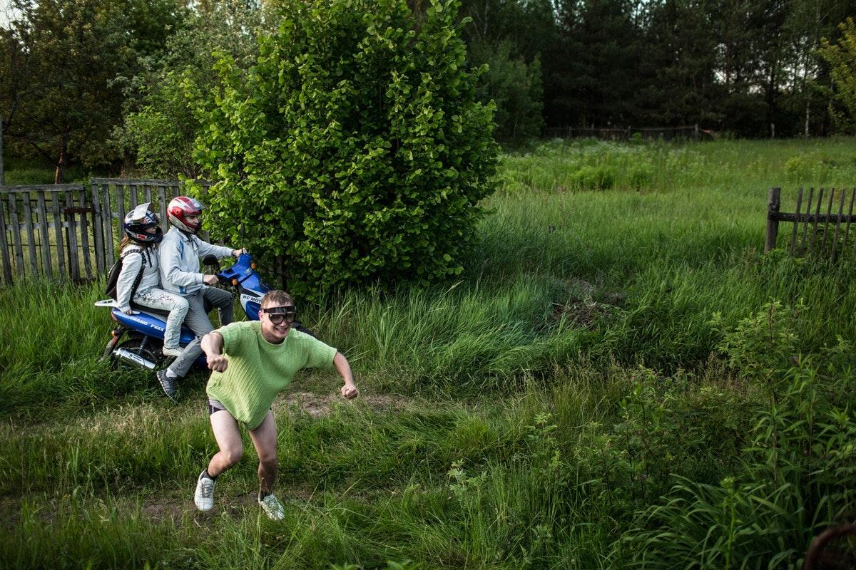 Белый ангел: Нильс Акерманн о любви и скуке рядом с Чернобыльской АЭС. Швейцарский фотограф Нильс Акерманн. Люди дурачатся на фоне зеленого поля. Интернет-журнал birdinflight.com.