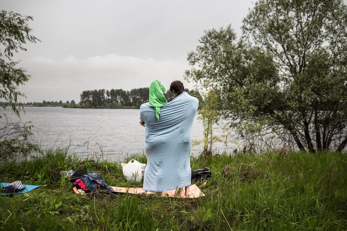 Белый ангел: Нильс Акерманн о любви и скуке рядом с Чернобыльской АЭС. Швейцарский фотограф Нильс Акерманн. Пара смотрит на реку, укутавшись в покрывало. Интернет-журнал birdinflight.com.
