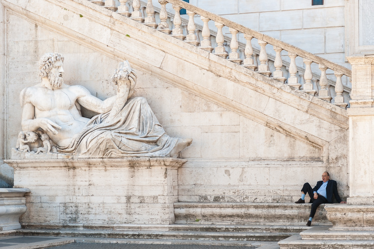 A man sits next to the monument outside Comune di Roma, Rome, Italy.