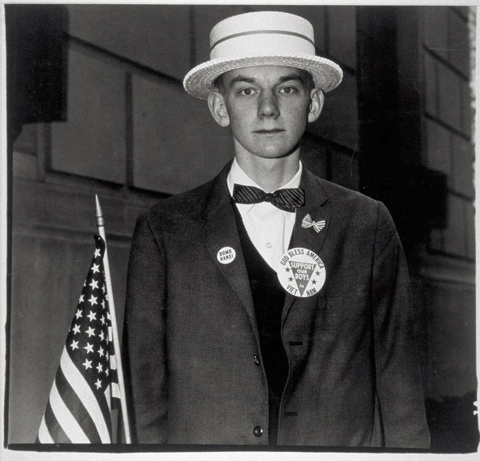 a-boy-with-straw-hat-and-flag-about-to-march-in-a-pro-war-parade