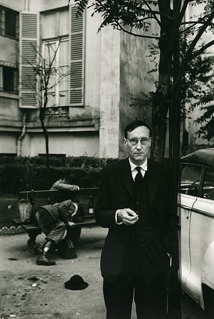 William Burroughs standing by an automobile and two drunks, photographed by Brion Gysin