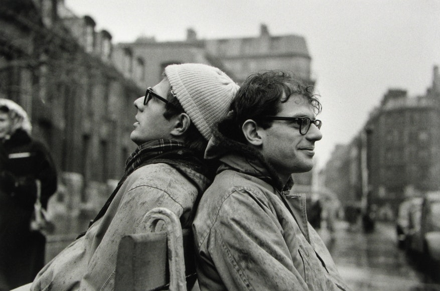 Peter Orlovsky (with hat) and Allen Ginsberg, on a double sided bench, Place St. Germain-des-Pres.