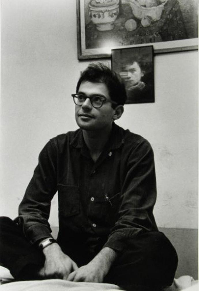 The American poet, Allen Ginsberg, in front of a portrait of Arthur Rimbaud.