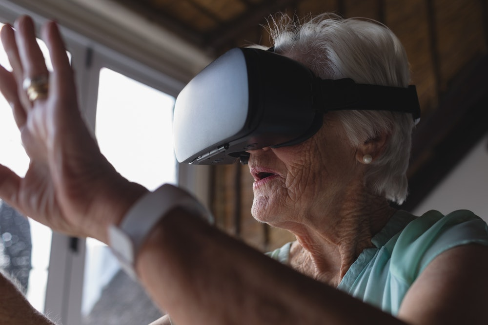 Close-up of a senior woman using virtual reality headset and raising her hand in living room at home